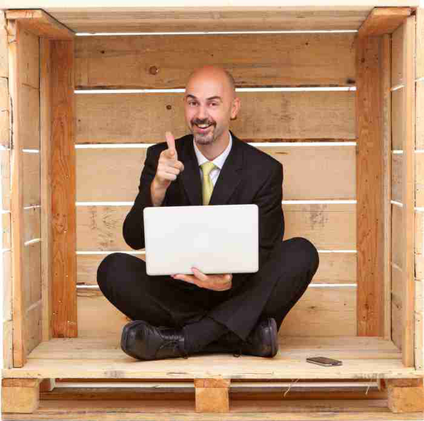Smiling manager with laptop sitting inside wood box